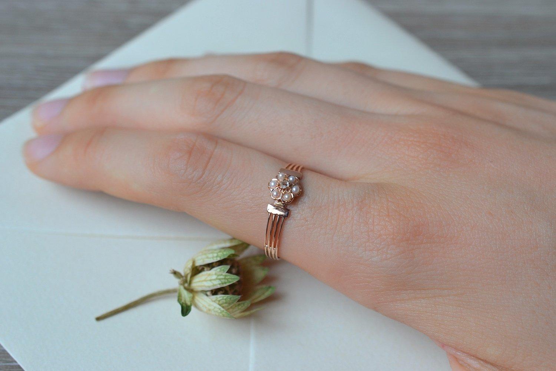 Bague en Or rose sertie d-un diamant entoure de perles blanches sur un anneau ajoure - bague de seconde main