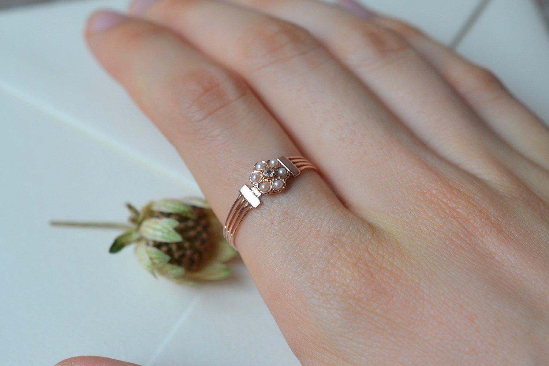 Bague en Or rose sertie d-un diamant entoure de perles blanches sur un anneau ajoure - bague retro